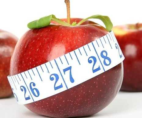 juicy red apple with a tape measure wrapped around it