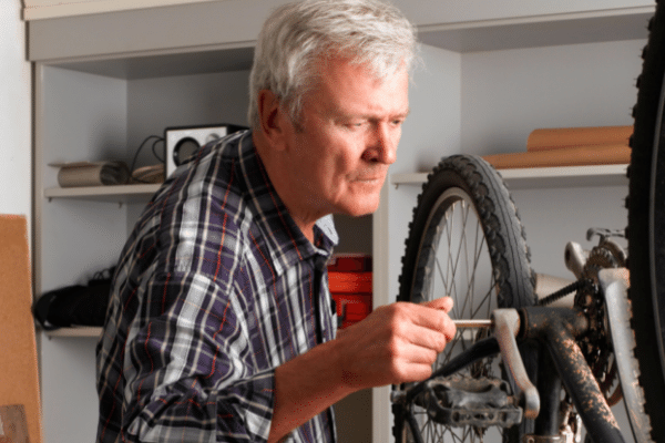 mature man in retirement mending a bicycle